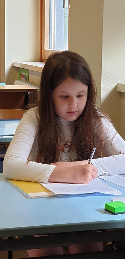 Bild: Ein Mädchen schreibt einen Brief